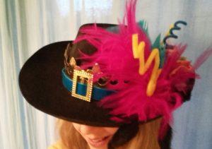 Visage caché sous un chapeau avec plumes et accessoires illustrant la Maison Dieu