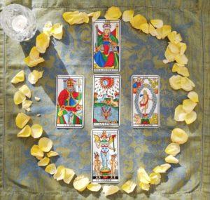 5 cartes de Tarot entourées de pétales de rose